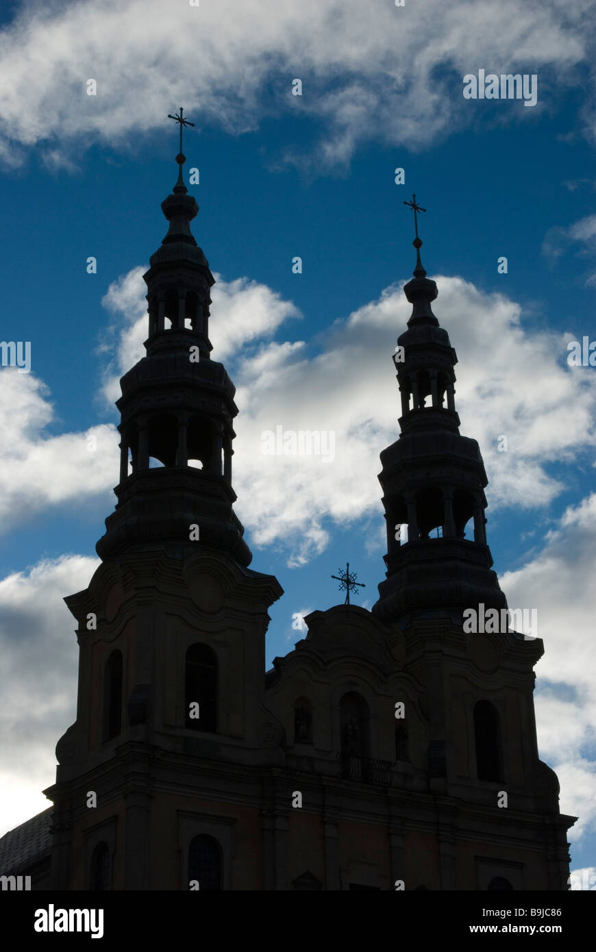 The twin spires of the Parish Church of St. Stanislaus silhouetted against deep blue sky, Poznan, Poland - Stock Image