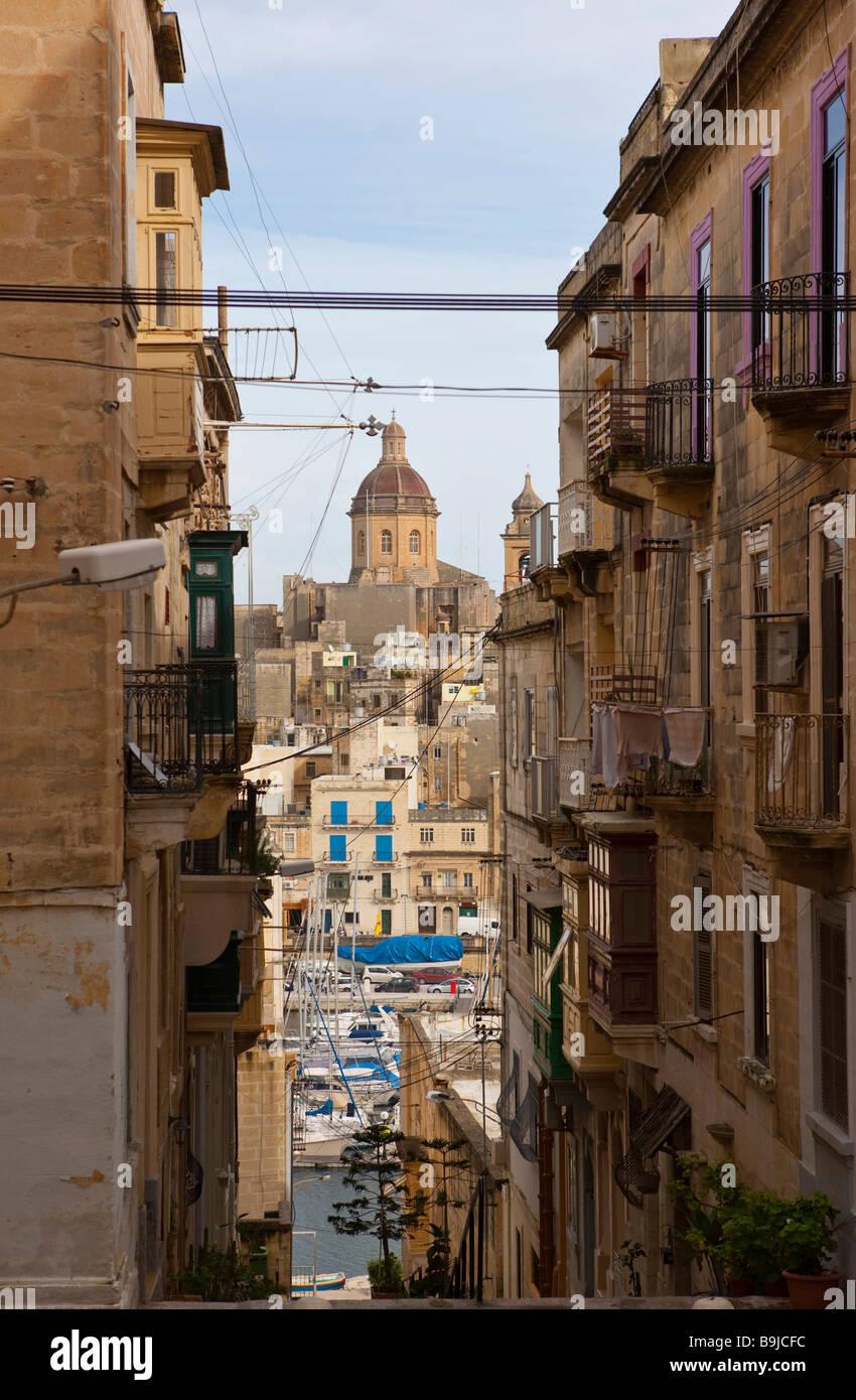View through old alleys in Senglea of the Sacra Infermeria Santa Skolastika Church in Vittoriosa Brigu, Malta, Europe - Stock Image