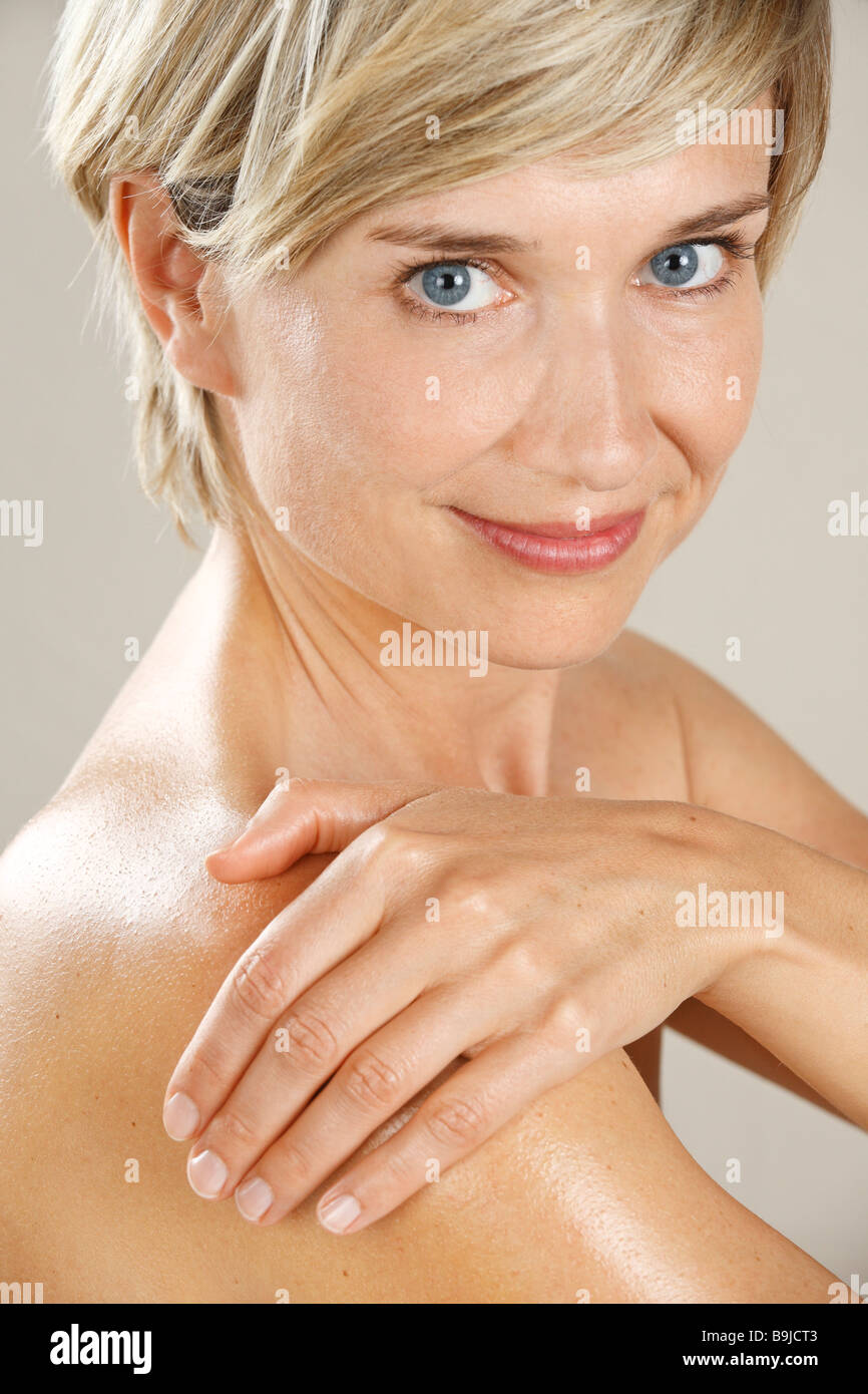 Woman rubbing her skin and shoulder with oil - Stock Image