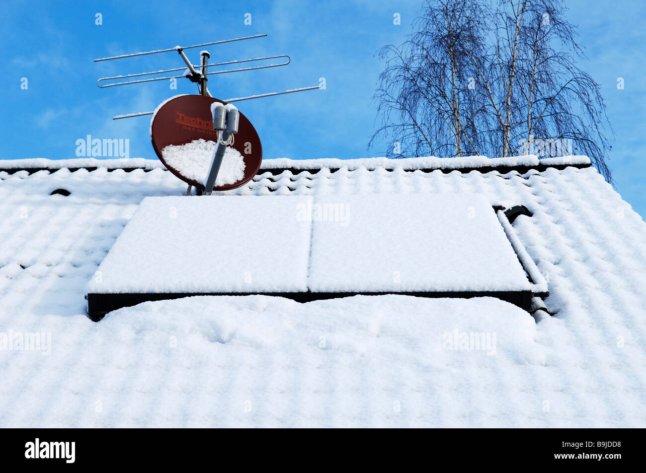 Snow-covered solar panels on a one-family-house, Eckental Valley, Middle Franconia, Bavaria, Germany, Europe - Stock Image