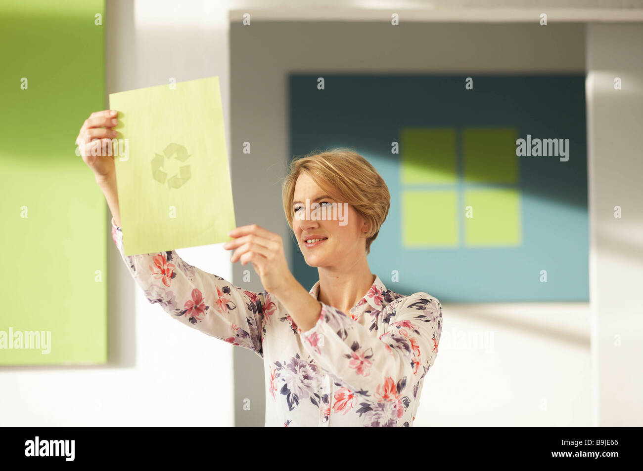 Woman looking at recycling logo - Stock Image