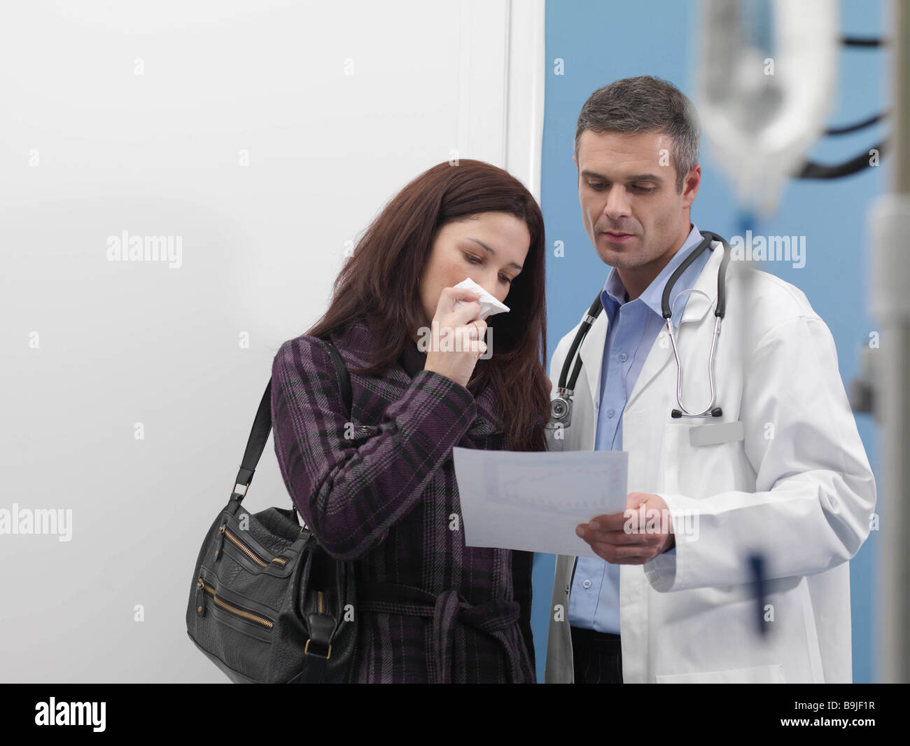 Doctor consoling a relative Stock Photo