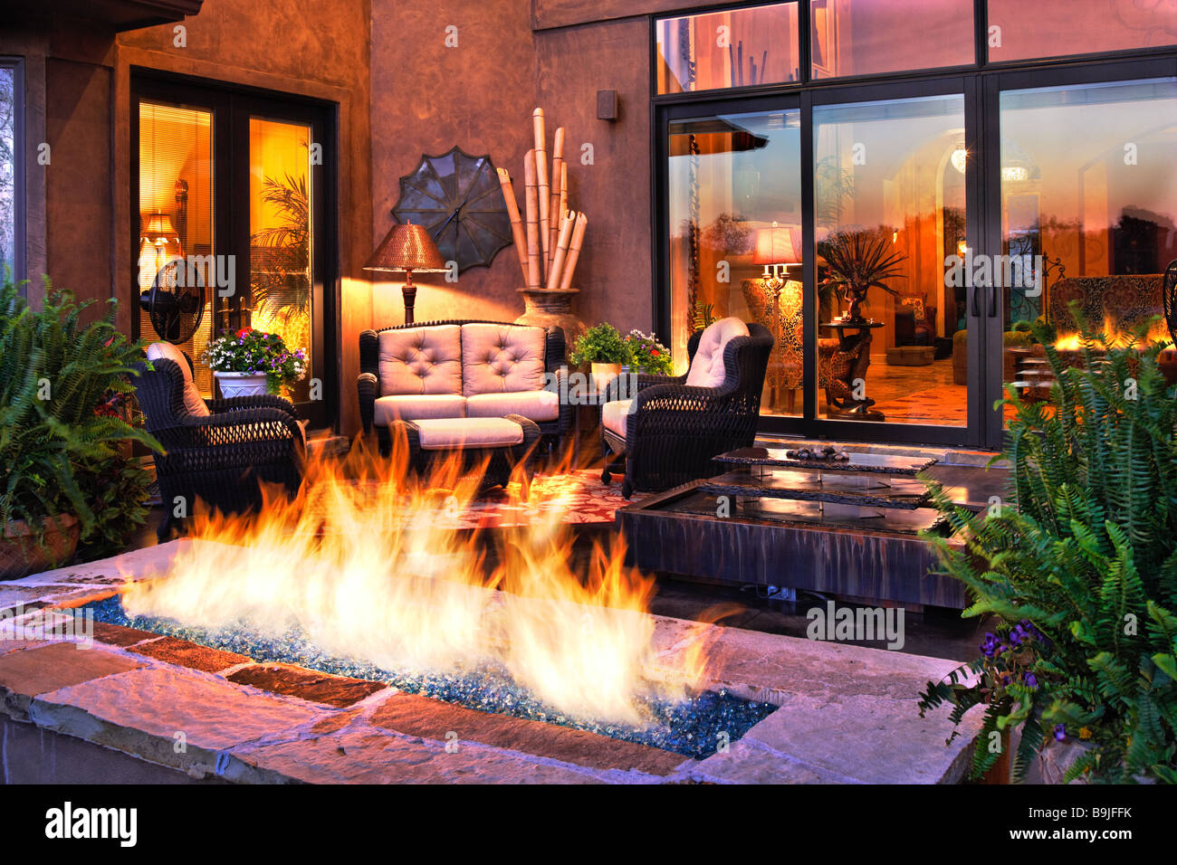 Gas Fireplace On Outdoor Patio. Flames Emerging From Rocks.