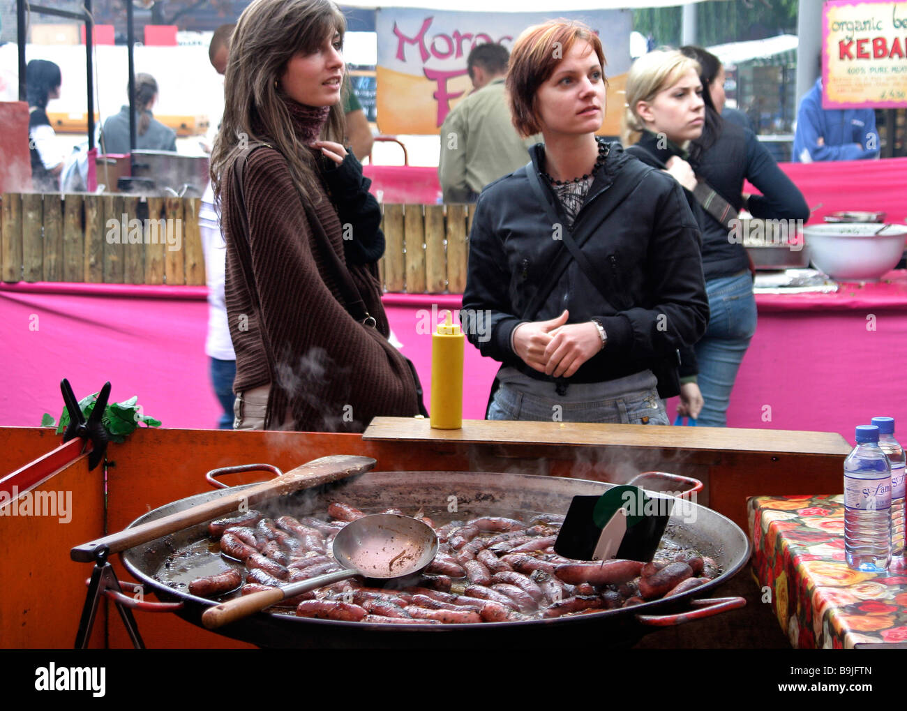 two tourists in Camden London market decide on food - Stock Image