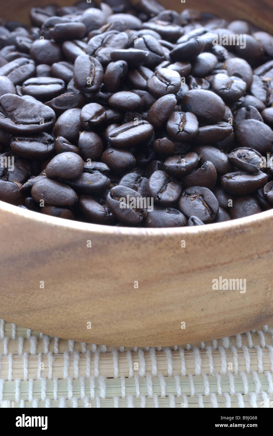 Roasted coffee beans in wooden cup - Stock Image