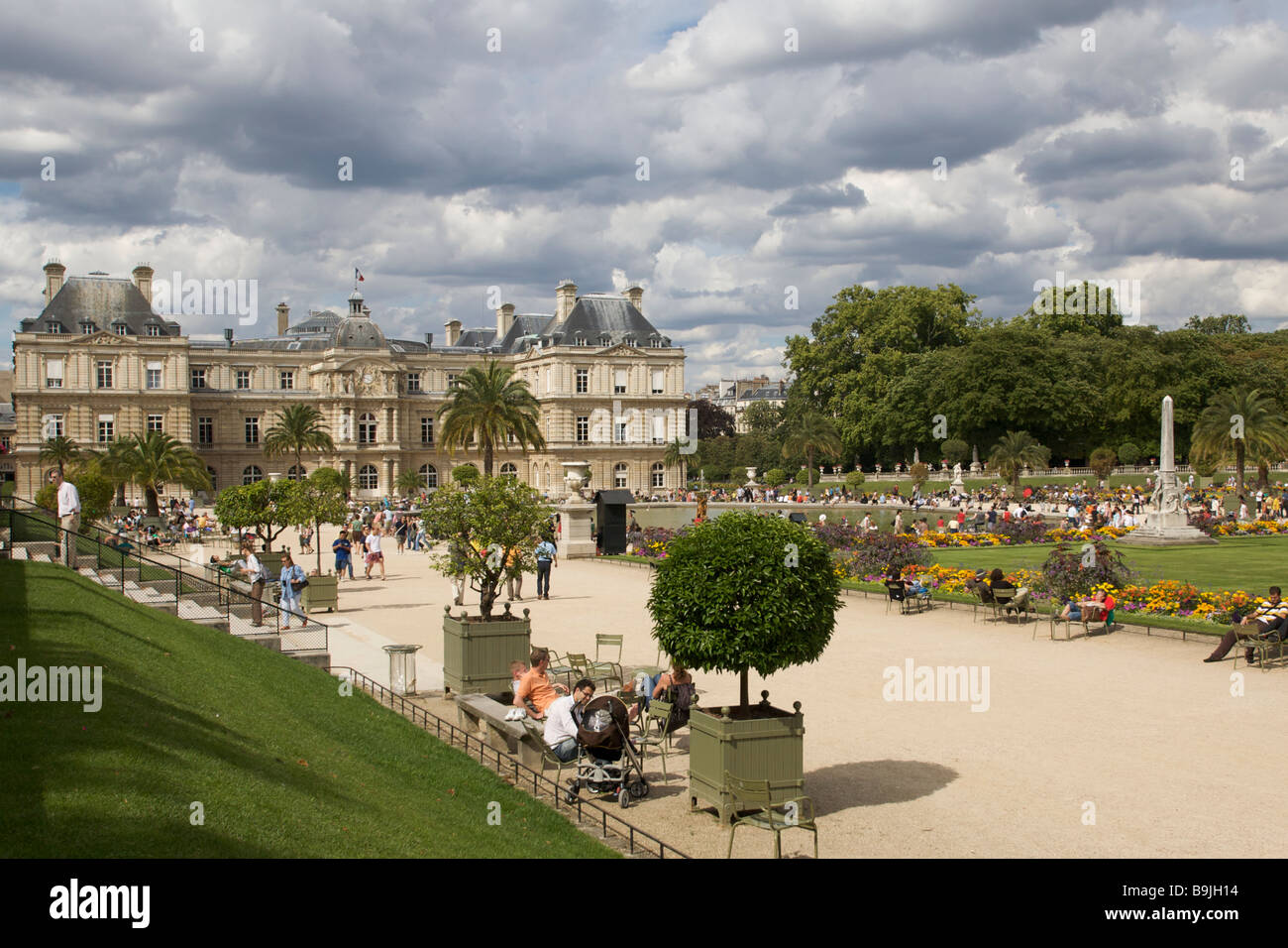 Looking to the Palais du Luxembourg in the Jardin du Luxembourg as people enjoy the public space in Paris France Stock Photo