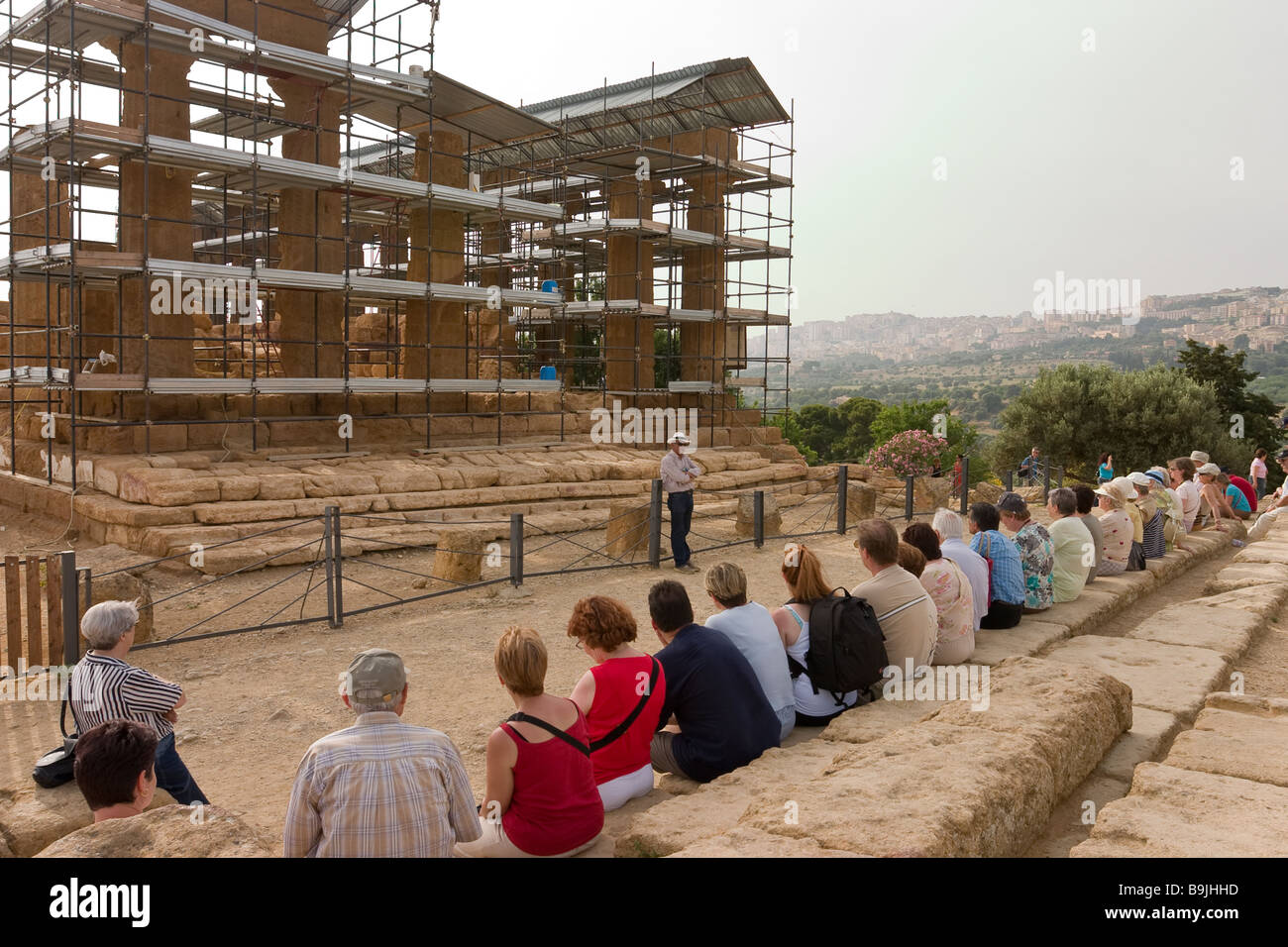 Tour Lecture. A tour group sits on ancient steps in front of the Temple of Juno Lacinia to have it described by - Stock Image