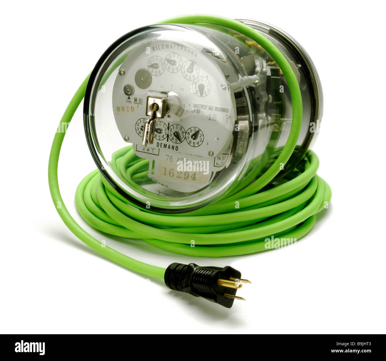 Electric power meter on a coiled green electrical extension cord and plug - Stock Image
