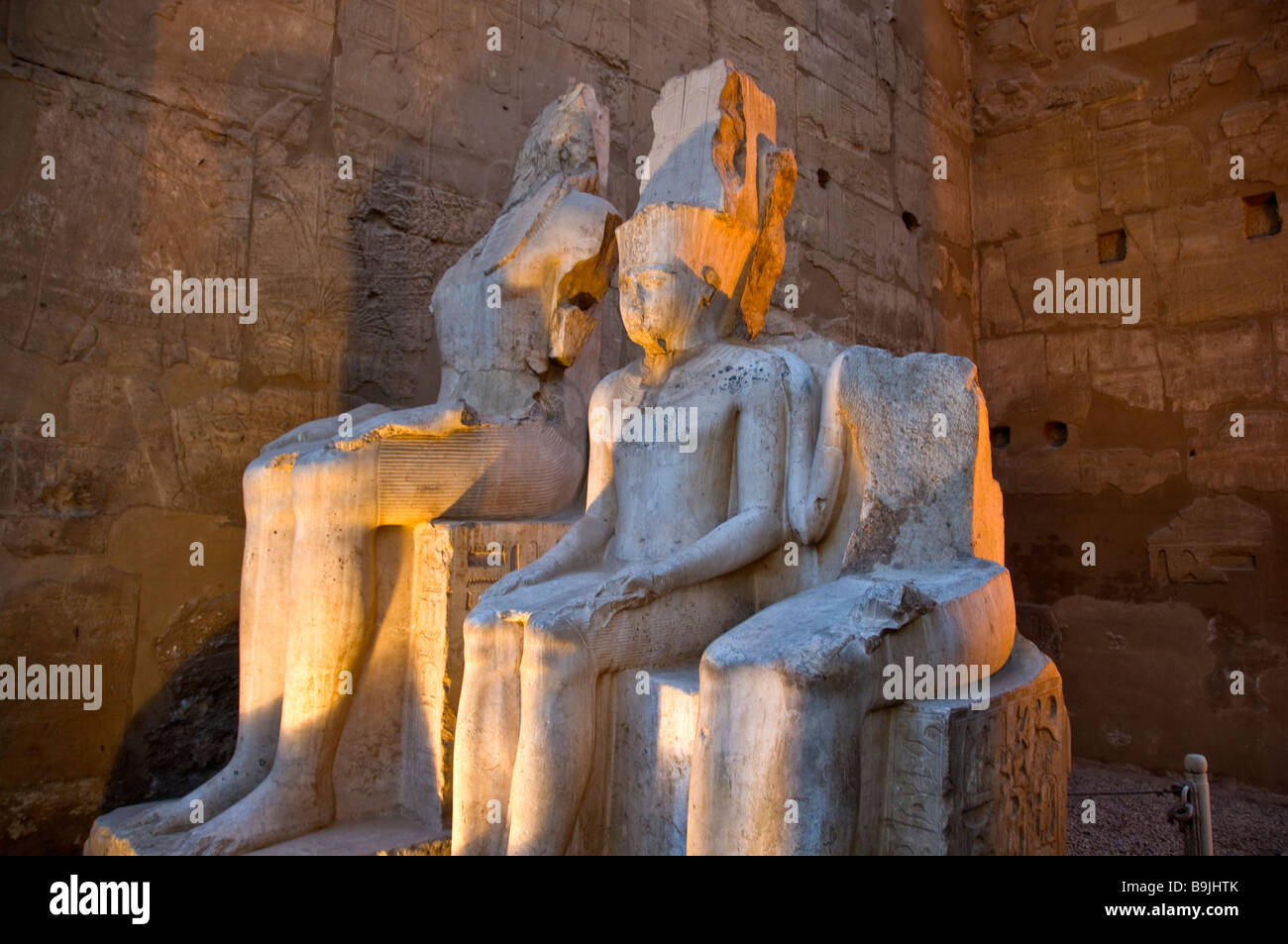 Luxor Temple Egypt night illuminated two defaced statues of royalty popular Egyptian tourist attraction - Stock Image