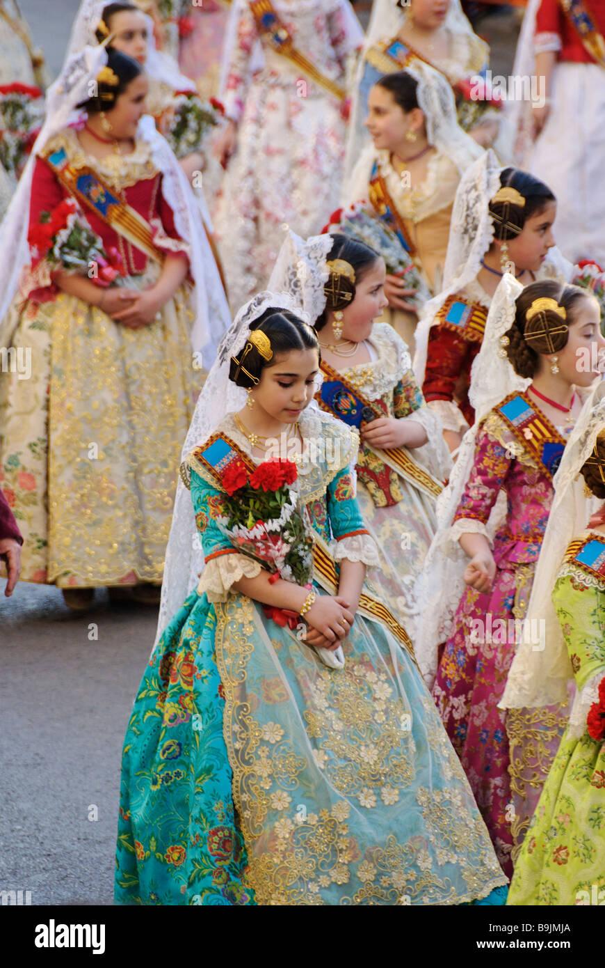 Young children Falleras parade towards Plaza de la Virgen with flower offerings. Las Fallas. Valencia Spain - Stock Image