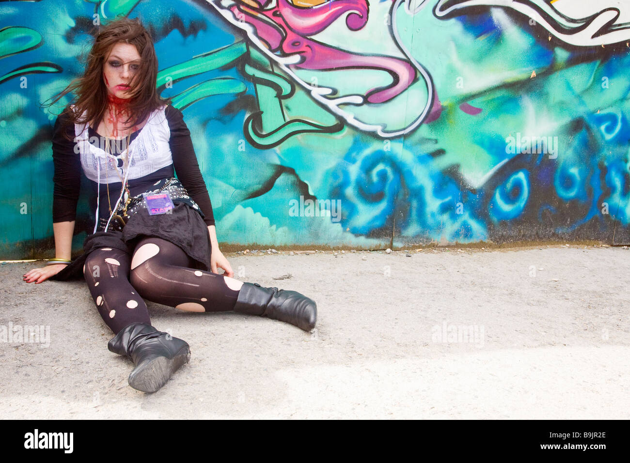 Young female teenage street theatre actress acts in horror story with fake blood Albert Dock Liverpool Lancashire - Stock Image