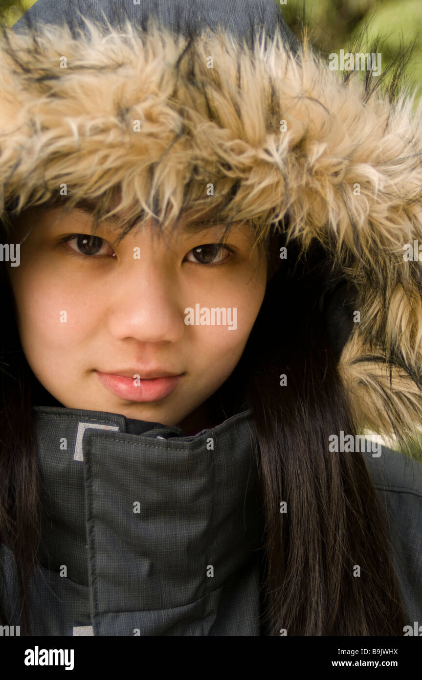 A young Asian-American woman wearing a black jacket with a fur-lined hood. - Stock Image