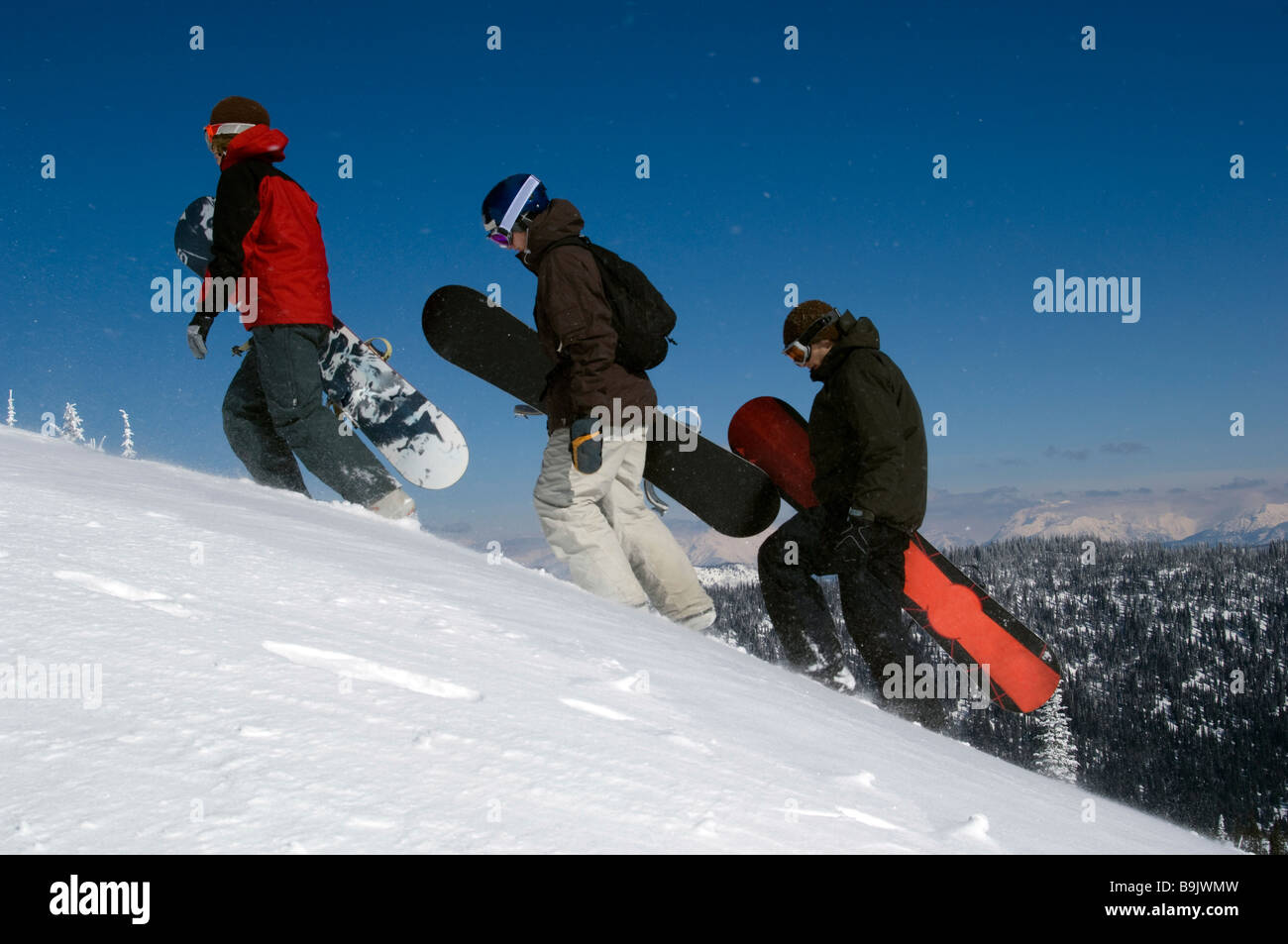 Three young men walk up a snowy mountain with their snowboards in the backcountry. - Stock Image