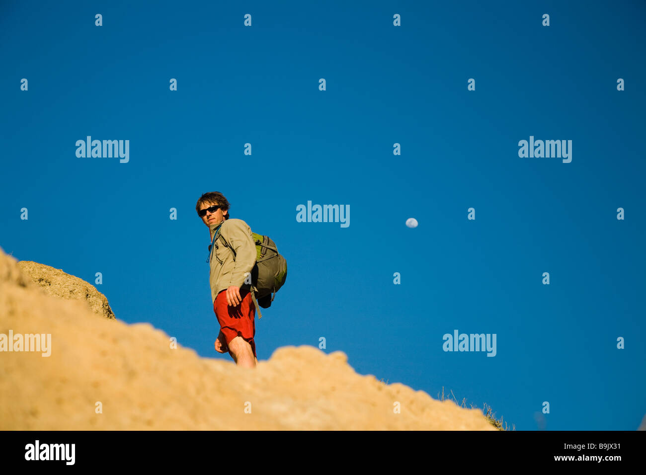 A portrait of a young man standing on a rock with a bright blue sky behind in Channel Islands National Park, California. - Stock Image
