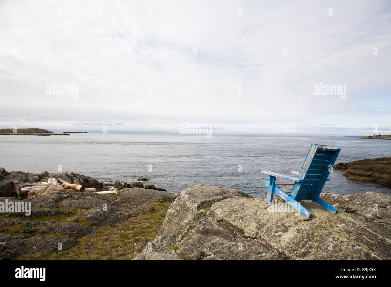 A lawn chair sits atop a rock outcrop overlooking the ocean on an overcast day in Victoria, British Columbia, Canada. Stock Photo