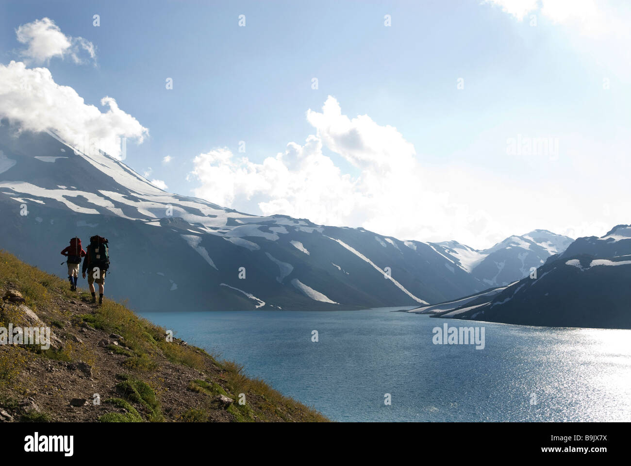 Two backpackers follow a trail around an alpine lake near the border of, Chile and Argentina. - Stock Image