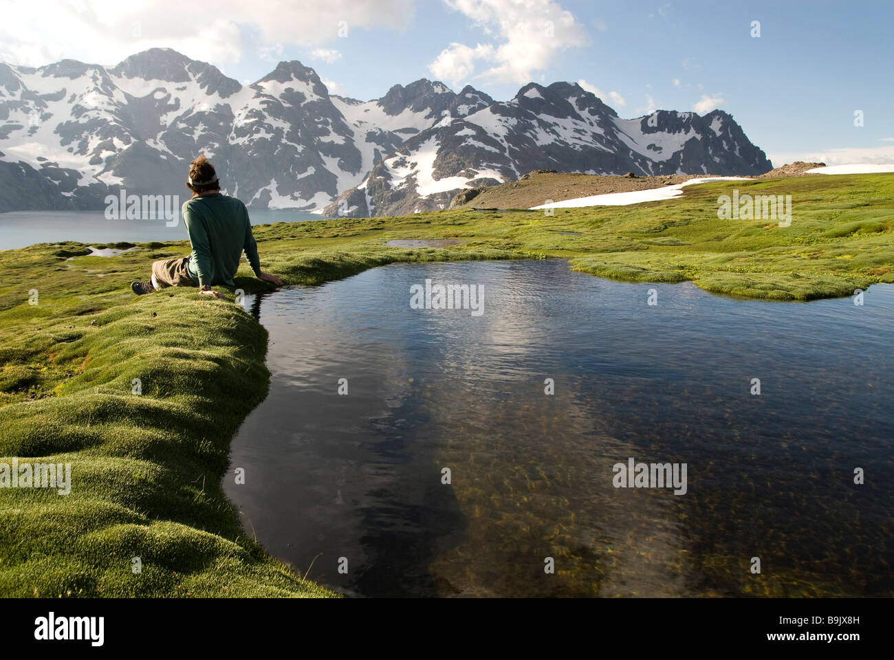 A young man sits next to a small pool enjoying a view of distant snow covered mountains. - Stock Image
