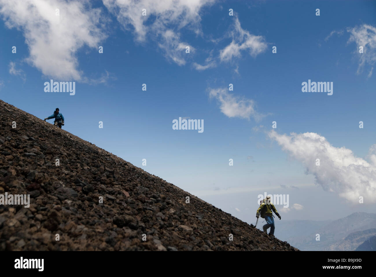 Two climbers descend a steep scree slope with a blue sky in the background. - Stock Image