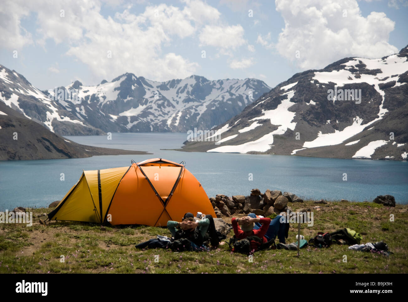 Two men rest next to their orange tent enjoying the dramatic views over a high alpine lake. - Stock Image