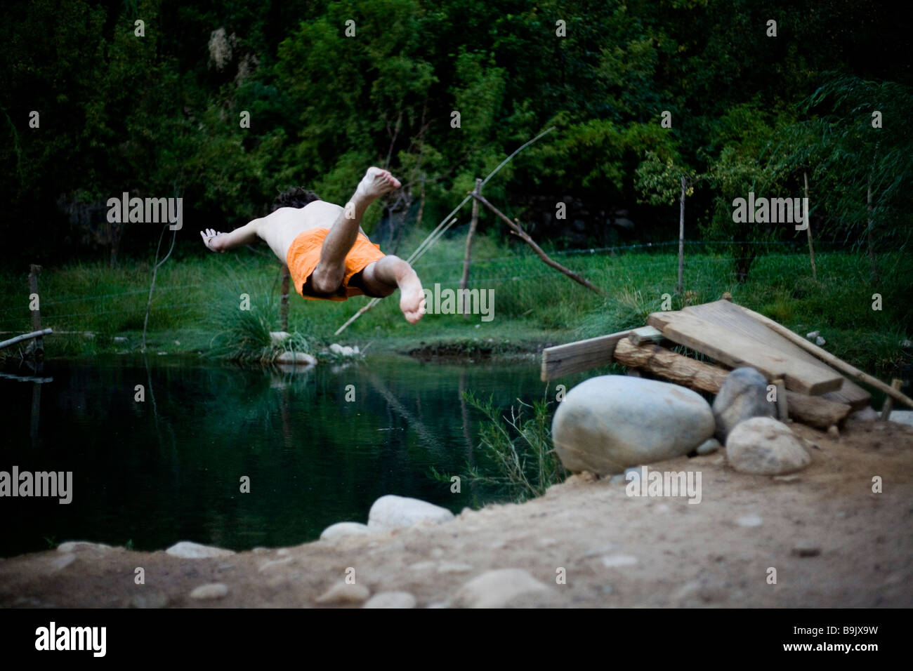 A young man dives into a small swimming hole. - Stock Image