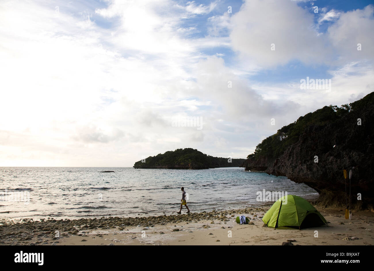 A man walks next to a green tent on an island in the Lau Group in Fiji, South Pacific. Stock Photo
