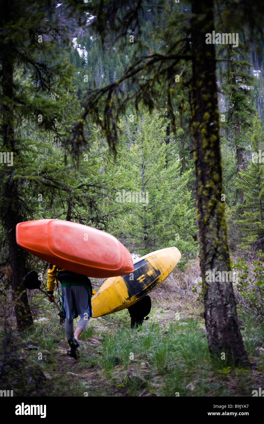 Two kayakers carry their boats through a dark forest to the put-in. - Stock Image