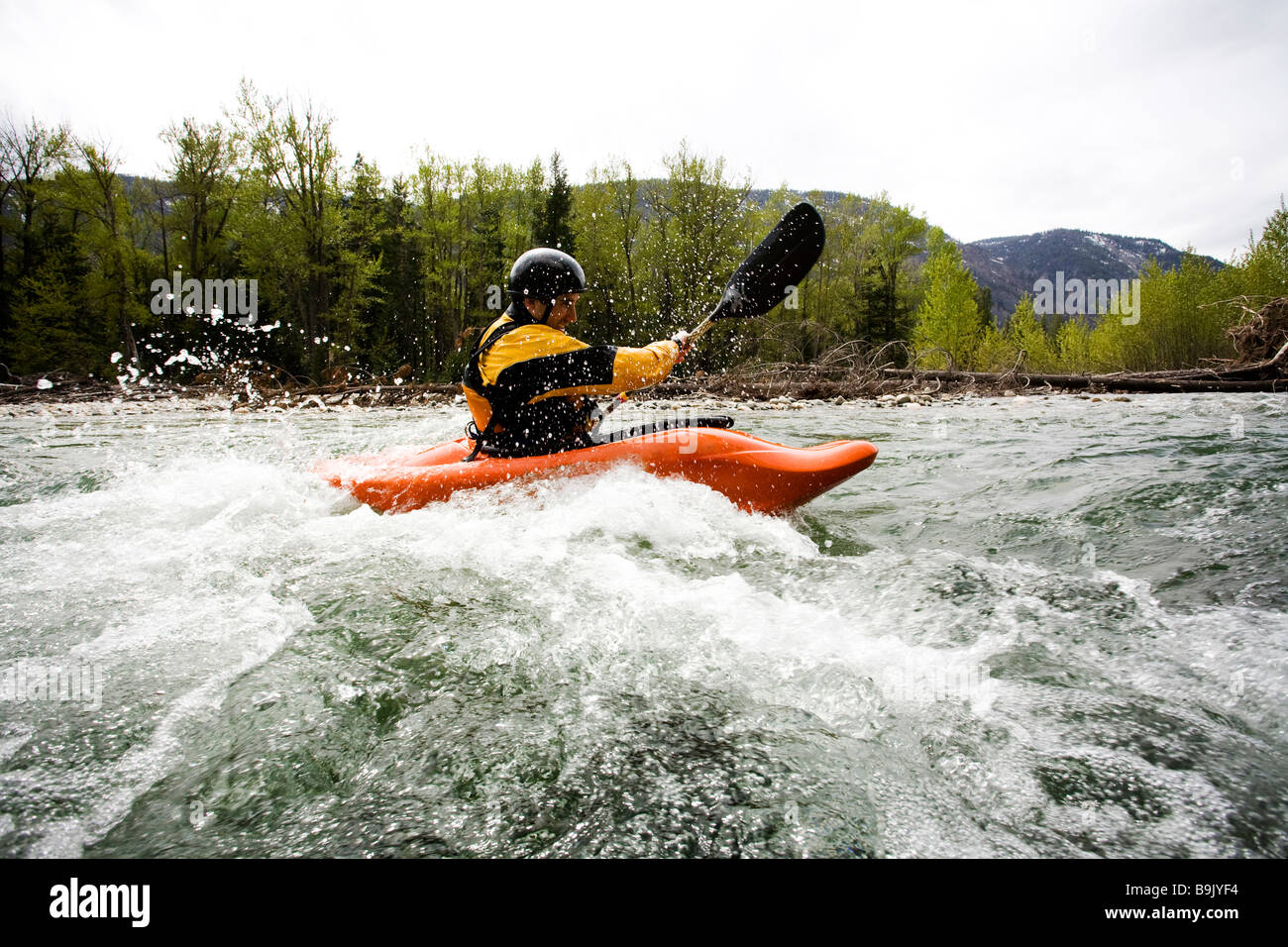 A playboater enjoys a small wave on a river. Stock Photo