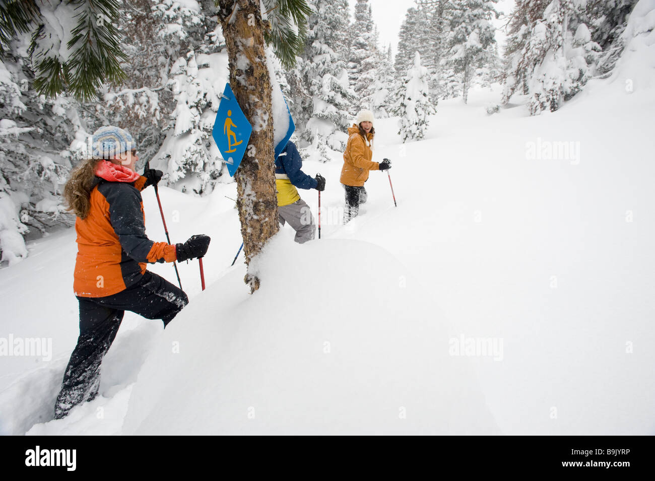 Rear view of three people in snowshoes with ski poles walking past a snowshoe trail sign in deep powder in Bend, - Stock Image