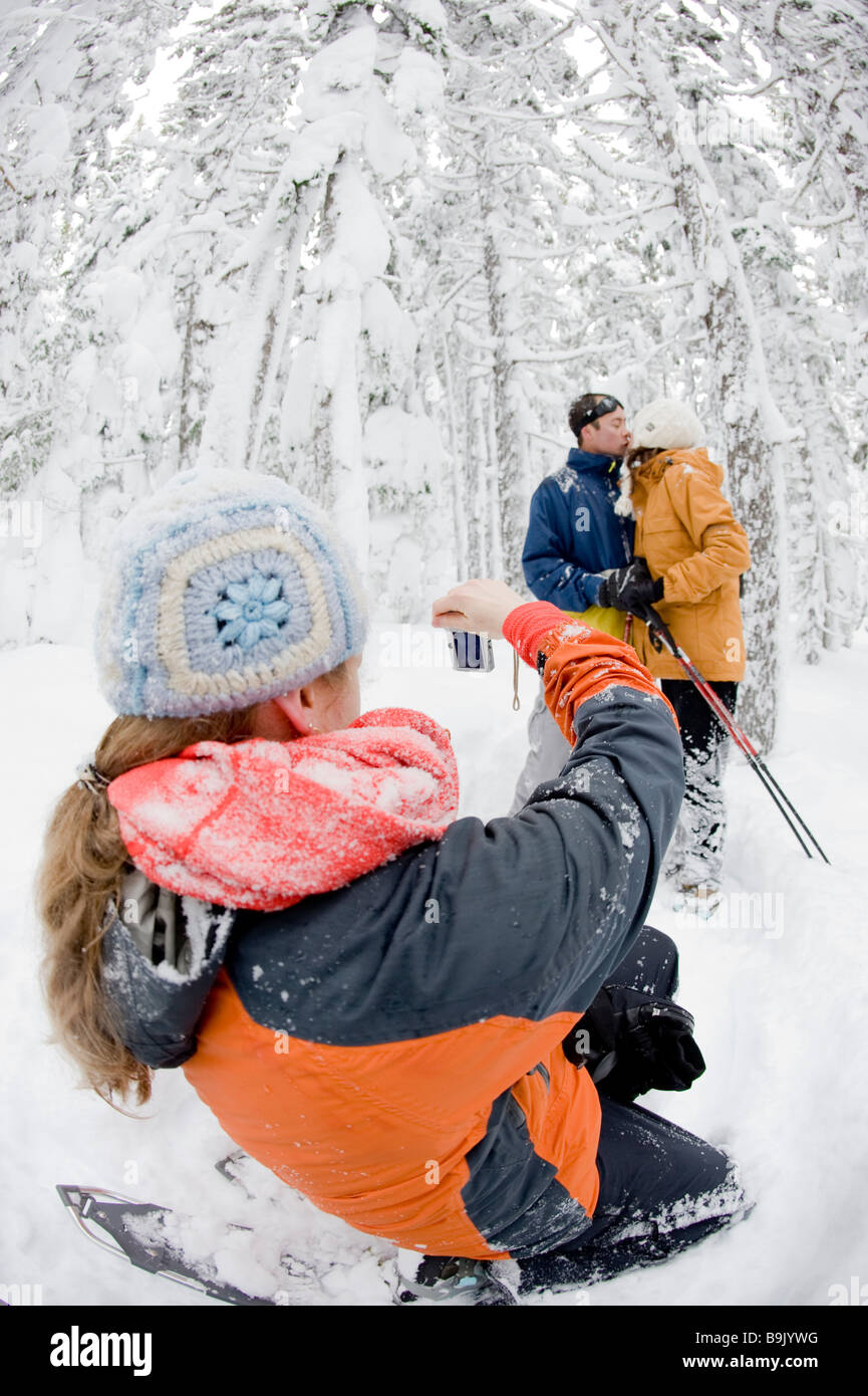 A mid adult woman and man pose while a young woman takes their picture while snowshoeing through a snow covered - Stock Image