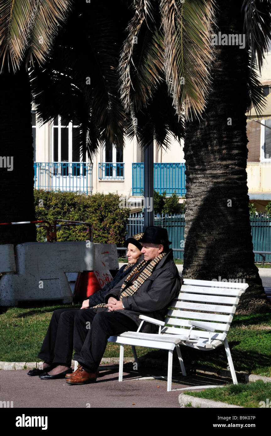 Nice France, 'Street Scene' 'Older Couple' Seniors Sitting on Public Bench on Sidewalk - Stock Image