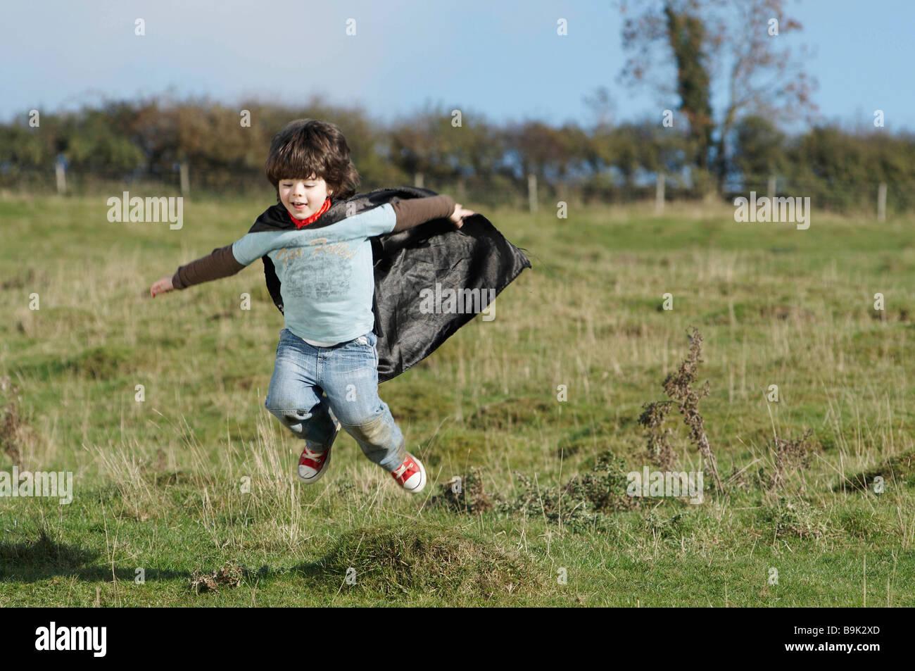 Super Hero boy in field - Stock Image