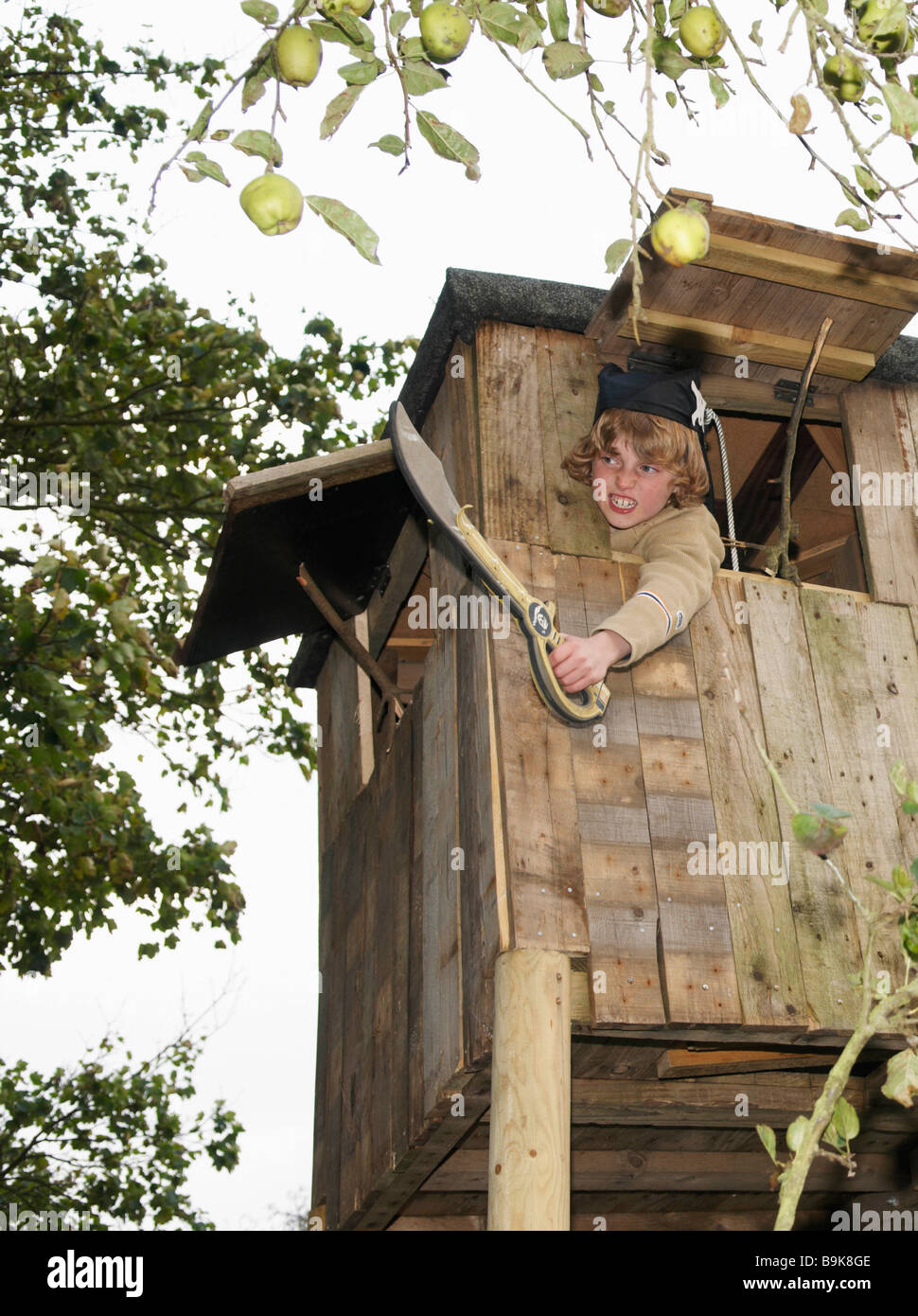 Boy playing in treehouse - Stock Image