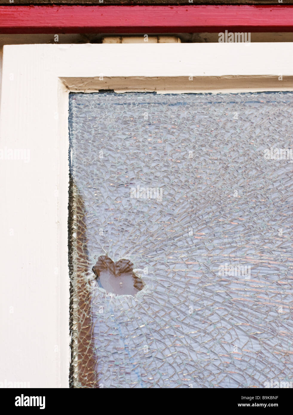 A smashed double glazed window caused by vandalism. - Stock Image