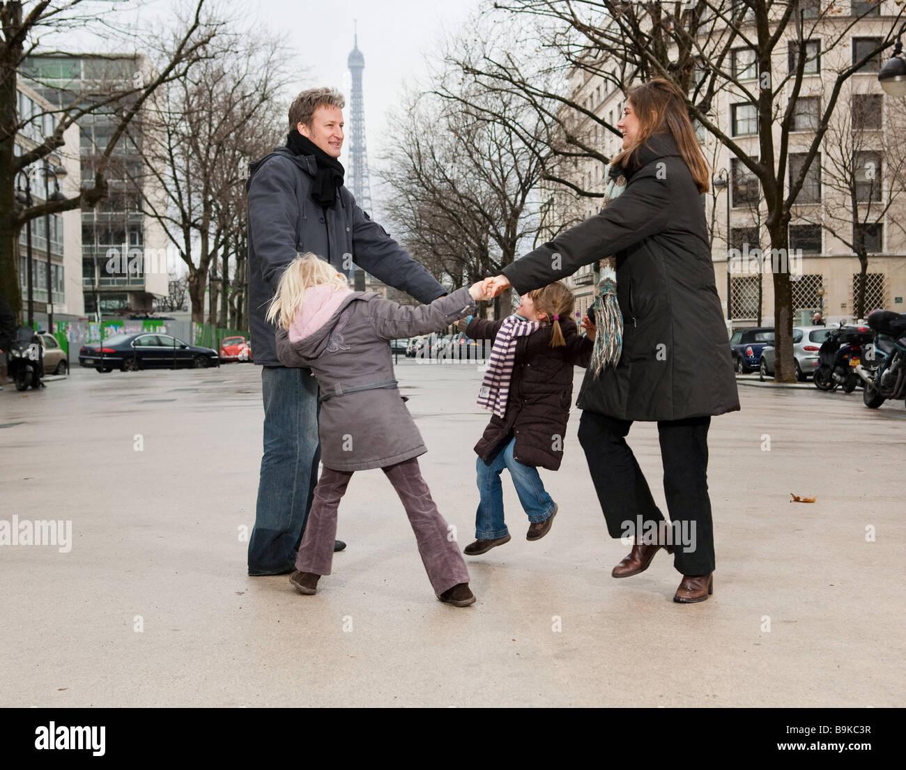 Family dancing near Eiffel Tower - Stock Image