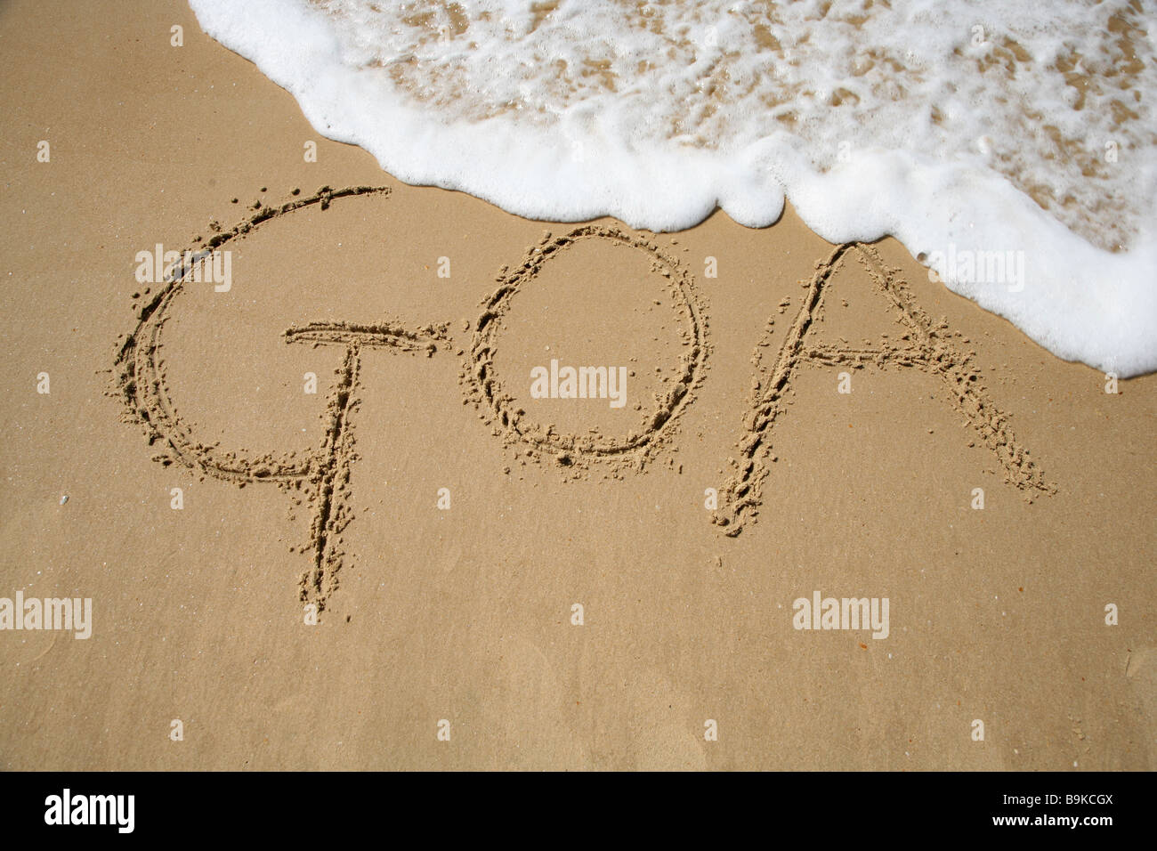 Goa written in the sand at Mobor Beach in Goa, India. - Stock Image