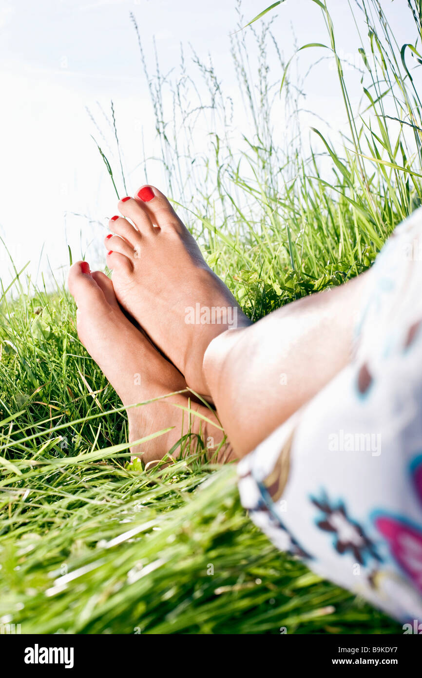 legs of woman relaxing in grass Stock Photo
