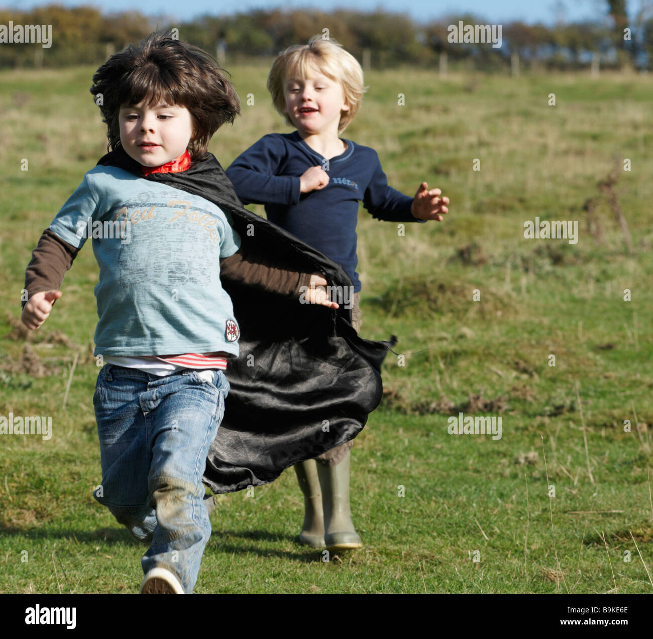 Super Hero boy and friend in field - Stock Image