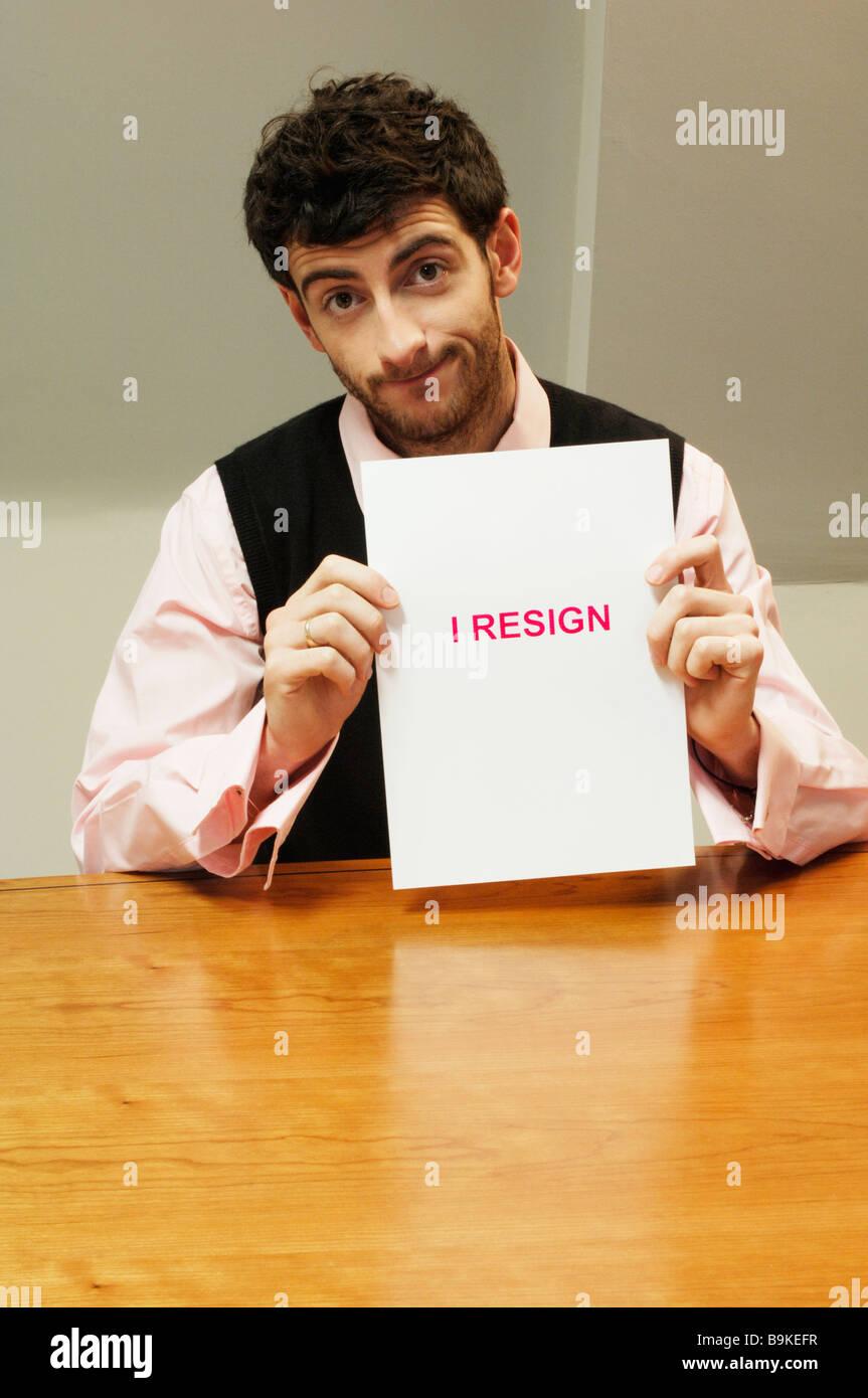 portrait of frustrated businessman sitting at desk holding resign document - Stock Image