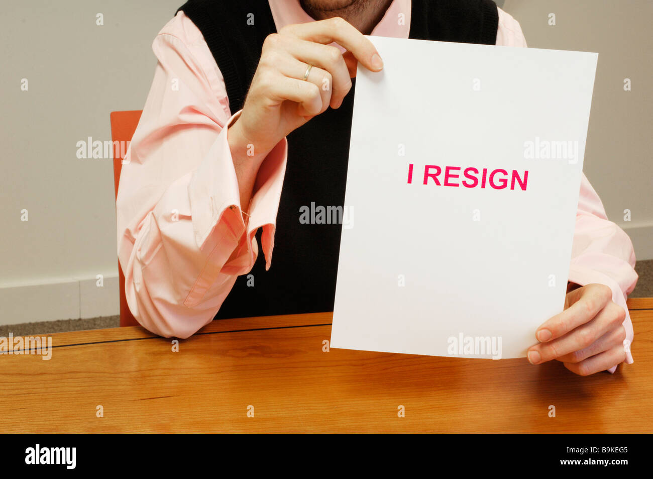 detail of businessman sitting at desk holding resign document - Stock Image