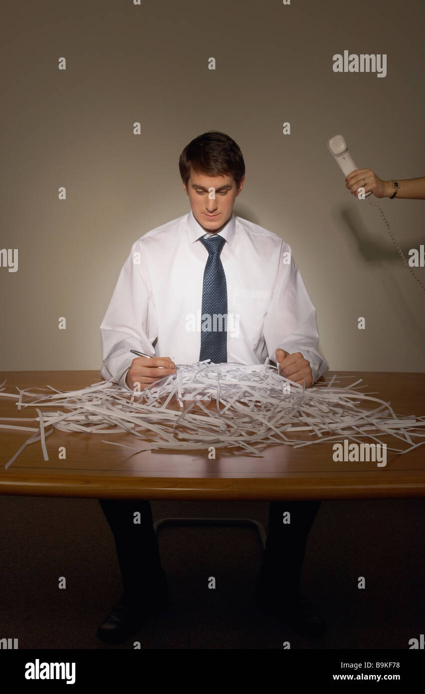 portrait of businessman sitting in front of shredded paper with female hand giving him telephone - Stock Image