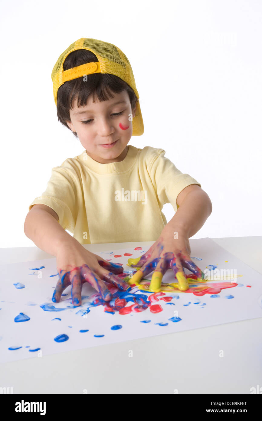 Little boy is making a finger painting - Stock Image