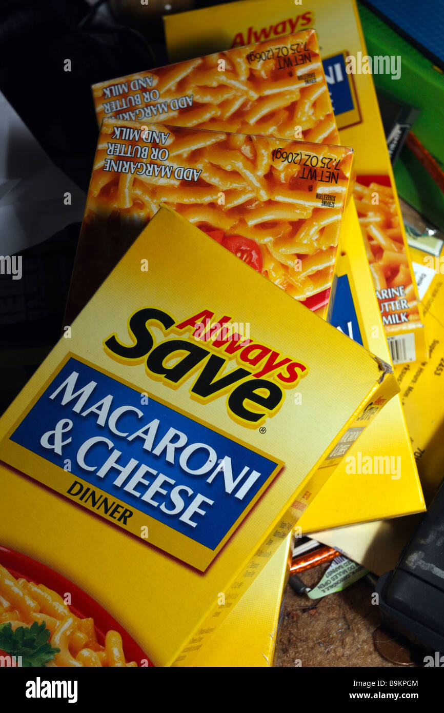 Always Save generic macaroni and cheese boxes, yellow, in dark surroundings. - Stock Image