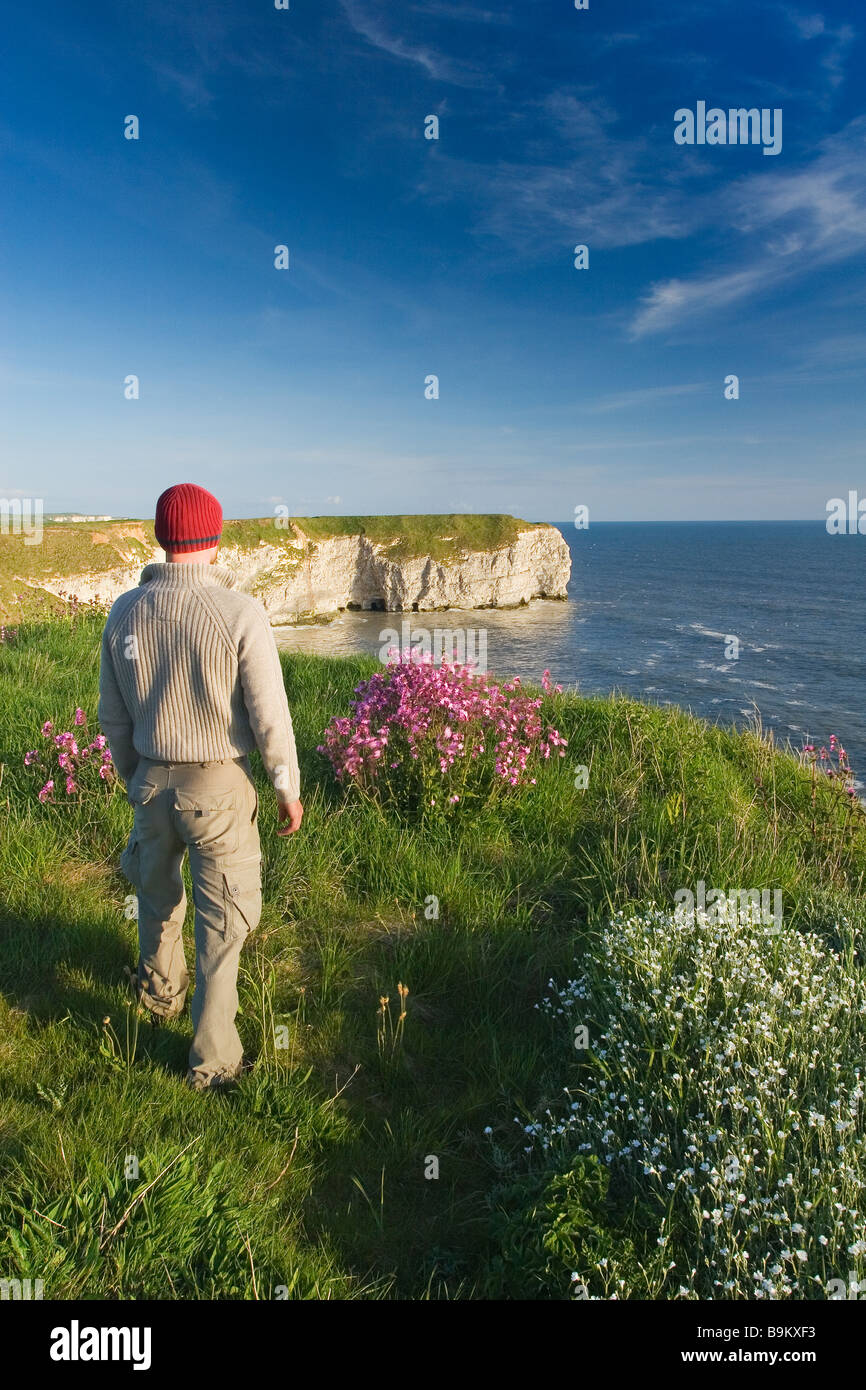 A visitor enjoying the view from the cliff tops on the Flamborough Headland Heritage Coast East Riding of Yorkshire - Stock Image