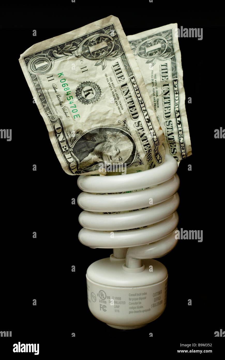 Energy saving lightbulb with two crumpled dollar bills stuck in the top in front of a black background - Stock Image