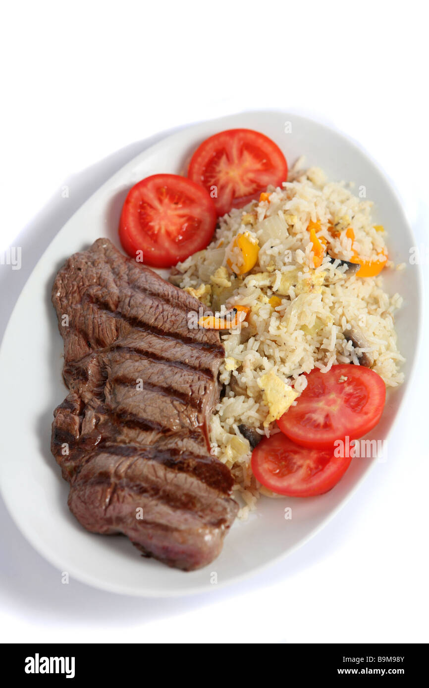 A meal of grilled steak with vegetable fried rice,a  fusion of eastern and western tastes. - Stock Image