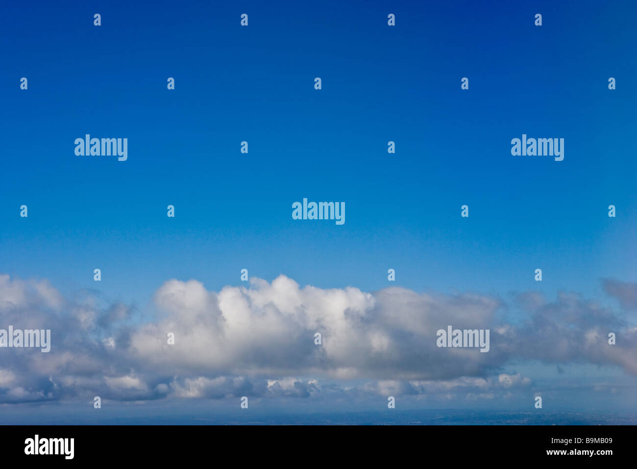 vivid blue shy with clouds from airplane - Stock Image