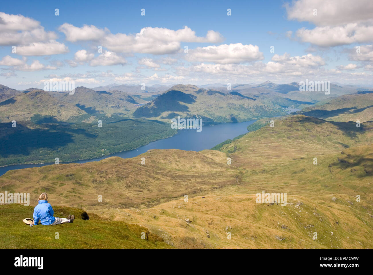 Woman eating her lunch while admiring the stunning view from the top of Ben Lomond, Stirlingshire, Scotland - Stock Image
