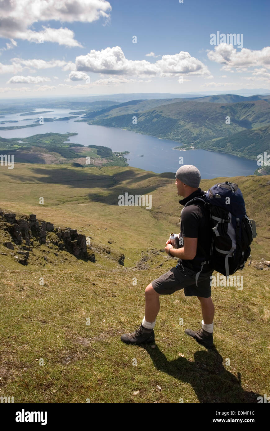 A hiker looks out at the stunning view from the summit of Ben Lomond on a bright sunny day, Stirlingshire, Scotland - Stock Image
