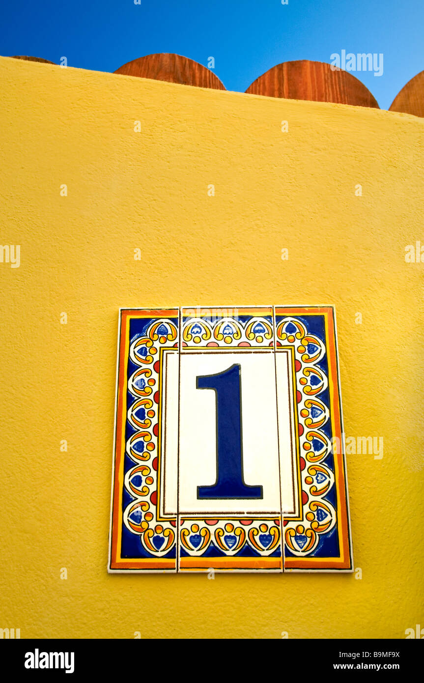 Ceramic decorative tiles 'Number 1' on yellow wall outside sunny holiday vacation resort Mediterranean house - Stock Image