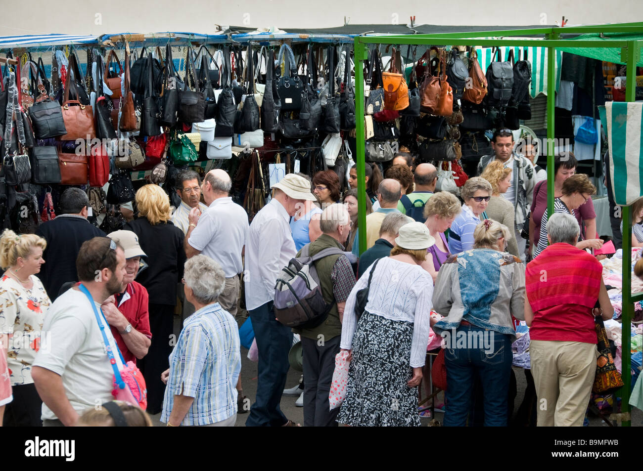 Tourists hunting for a bargain in popular Los Cristianos Sunday market with leather goods on display Tenerife Canary - Stock Image